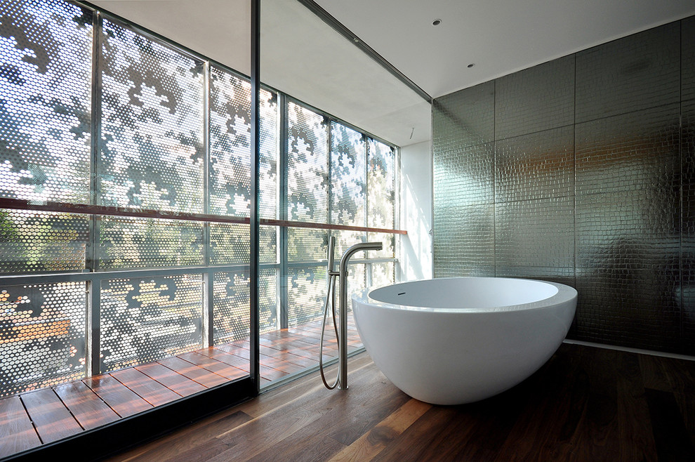 Trendy dark wood floor freestanding bathtub photo in London