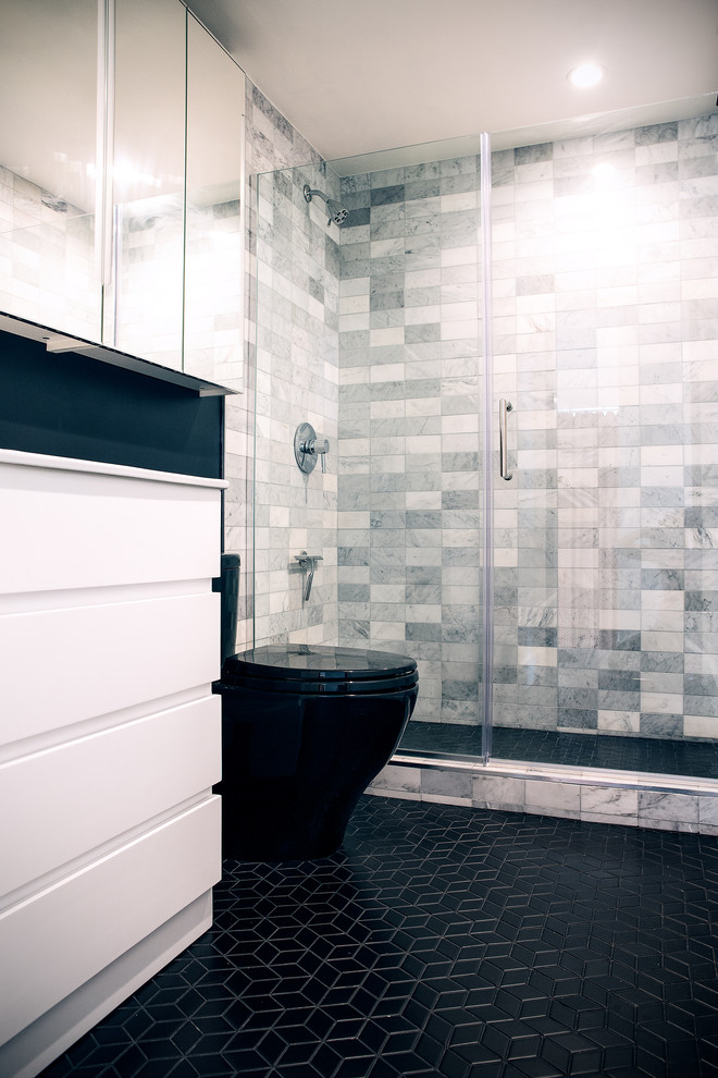 Corner shower - small contemporary master gray tile and marble tile ceramic tile and black floor corner shower idea in San Francisco with flat-panel cabinets, white cabinets, a one-piece toilet, black walls, an integrated sink, a hinged shower door and white countertops