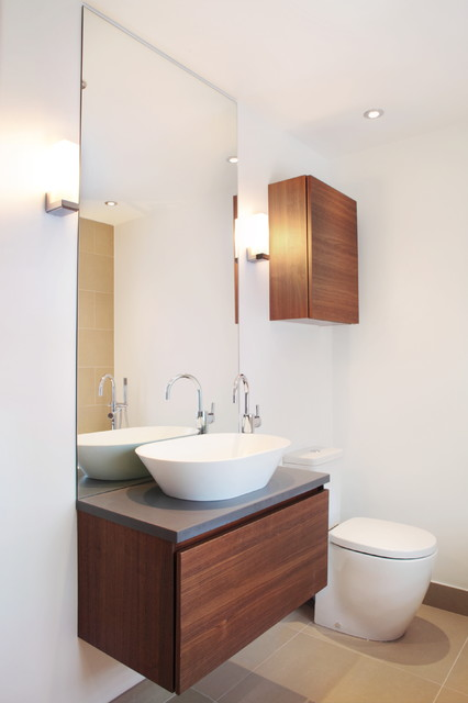 Imagen de cuarto de baño actual, de tamaño medio, con armarios con paneles lisos, encimera de acrílico, puertas de armario de madera en tonos medios y paredes blancas