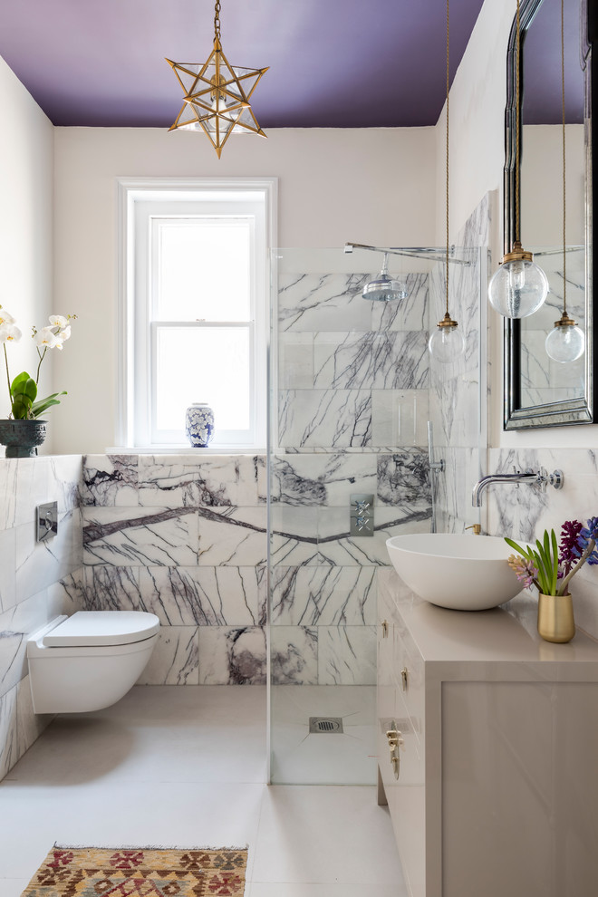 Inspiration for a mid-sized transitional 3/4 white tile and stone tile porcelain floor wet room remodel in London with furniture-like cabinets, gray cabinets, a wall-mount toilet, white walls, a vessel sink and wood countertops