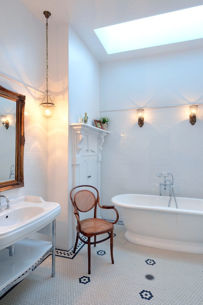 Ornate white tile mosaic tile floor freestanding bathtub photo in Wollongong with a console sink and white walls