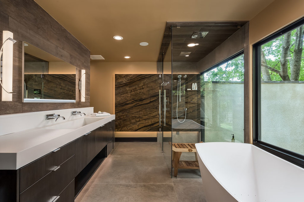 Bathroom - large contemporary master brown tile porcelain tile and gray floor bathroom idea in Columbus with flat-panel cabinets, dark wood cabinets, beige walls, an integrated sink, concrete countertops and a hinged shower door