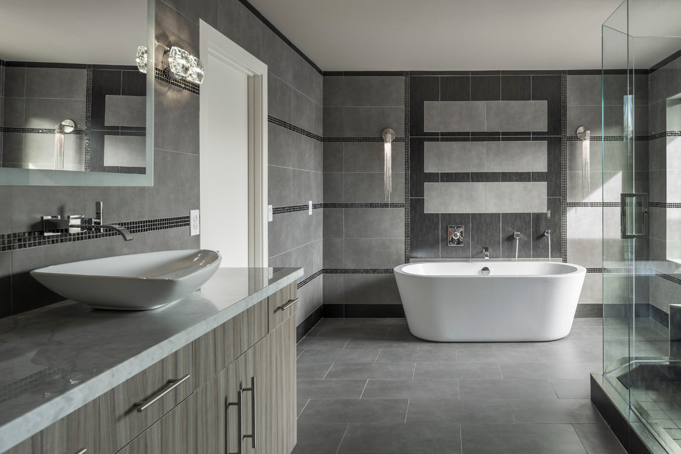 Example of a large trendy master gray tile and porcelain tile porcelain floor bathroom design in Phoenix with a vessel sink, flat-panel cabinets, gray cabinets, marble countertops, a one-piece toilet and gray walls