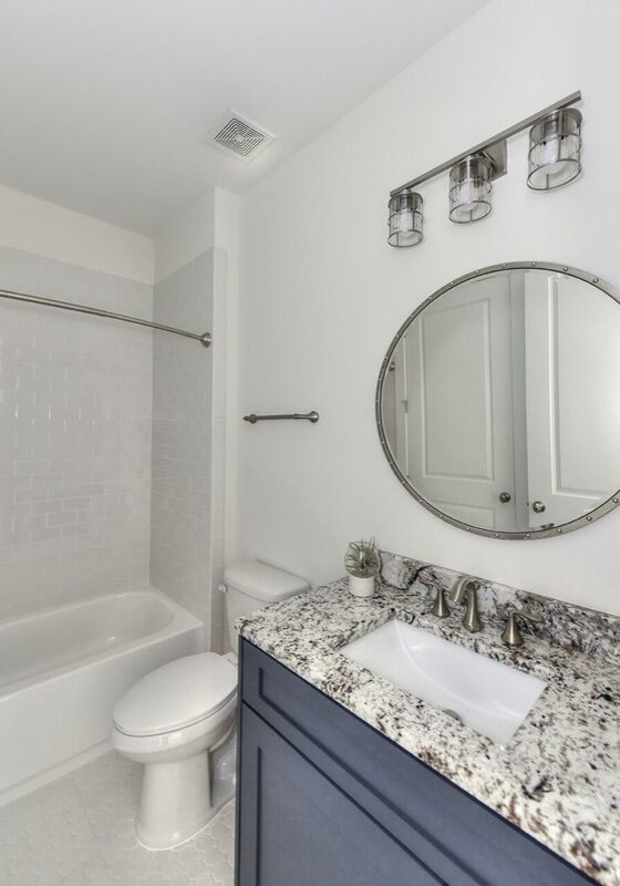 Inspiration for a mid-sized coastal 3/4 white tile and subway tile porcelain tile and white floor bathroom remodel in Jacksonville with shaker cabinets, gray cabinets, a two-piece toilet, white walls, an undermount sink, granite countertops and multicolored countertops