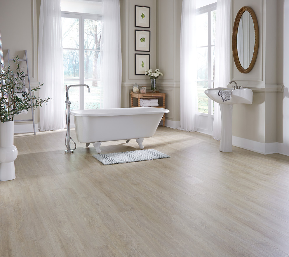 Inspiration for a mid-sized contemporary master medium tone wood floor and beige floor claw-foot bathtub remodel in Other with beige walls and a pedestal sink