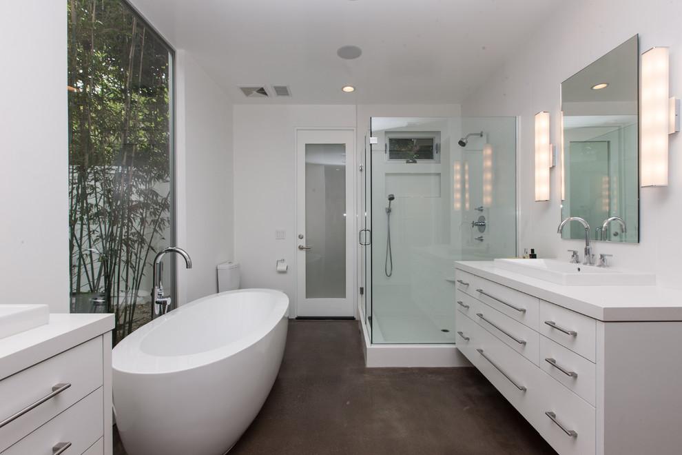 Modelo de cuarto de baño principal, contemporáneo, grande, con armarios con paneles lisos, puertas de armario blancas, bañera exenta, ducha esquinera, baldosas y/o azulejos blancos, paredes blancas, suelo de cemento, lavabo encastrado, suelo marrón y ducha con puerta con bisagras