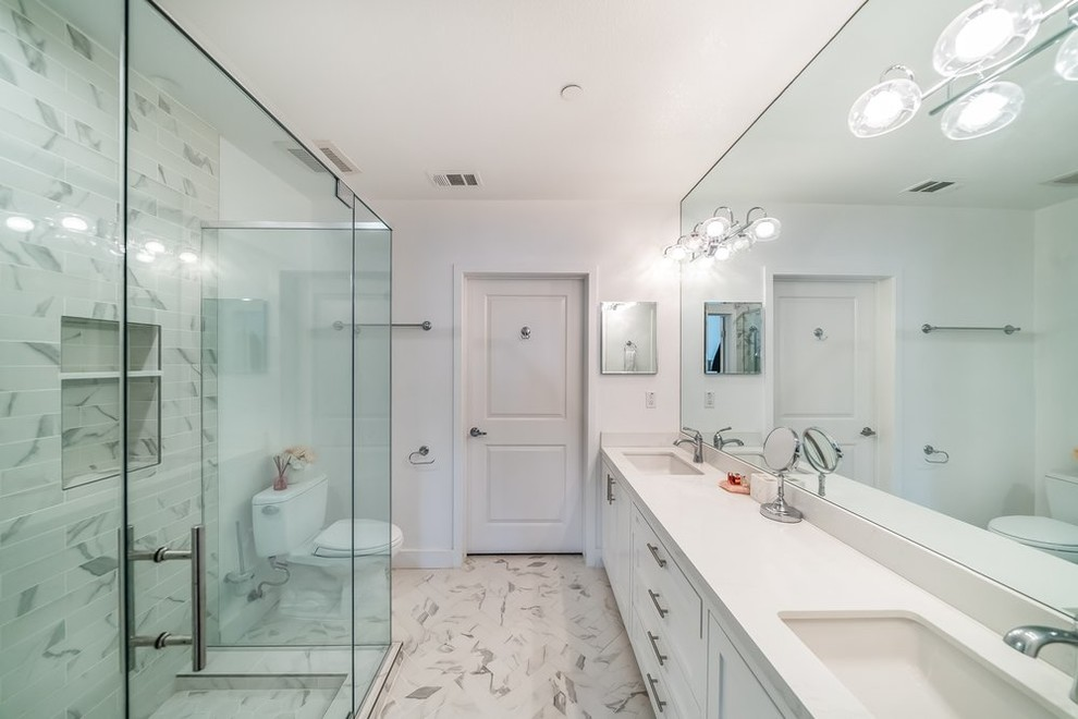 Example of a mid-sized transitional white tile and subway tile marble floor and gray floor bathroom design in Orange County with recessed-panel cabinets, white cabinets, a two-piece toilet, white walls, a vessel sink, quartz countertops and gray countertops
