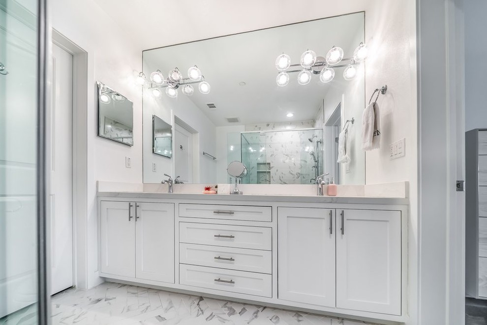 Inspiration for a mid-sized transitional white tile and subway tile marble floor and gray floor bathroom remodel in Orange County with recessed-panel cabinets, white cabinets, a two-piece toilet, white walls, a vessel sink, quartz countertops and gray countertops