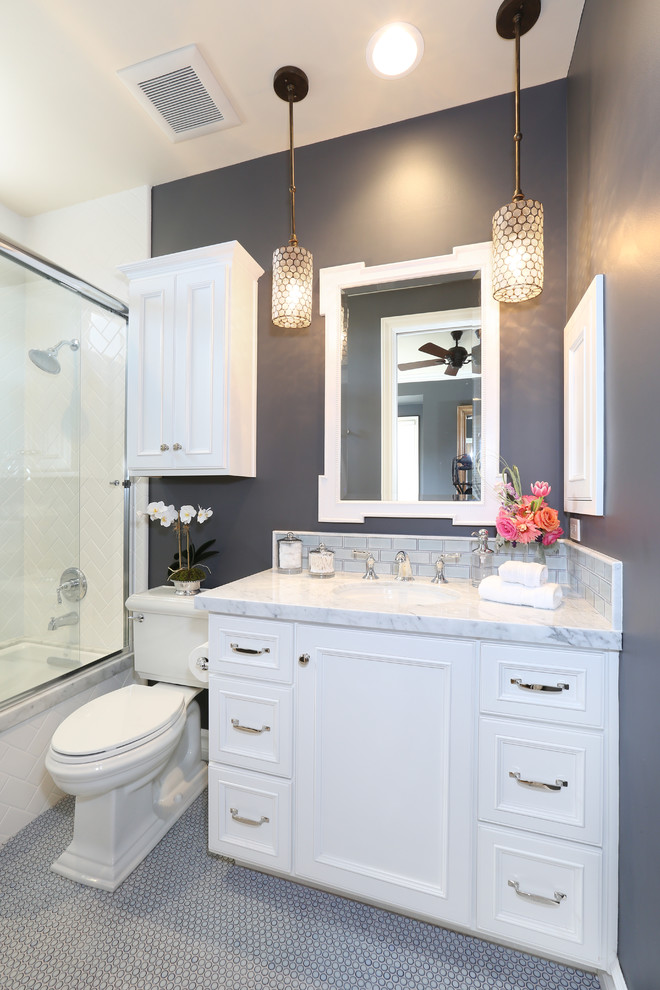 Elegant bathroom photo in Orange County with a two-piece toilet, white cabinets and gray walls