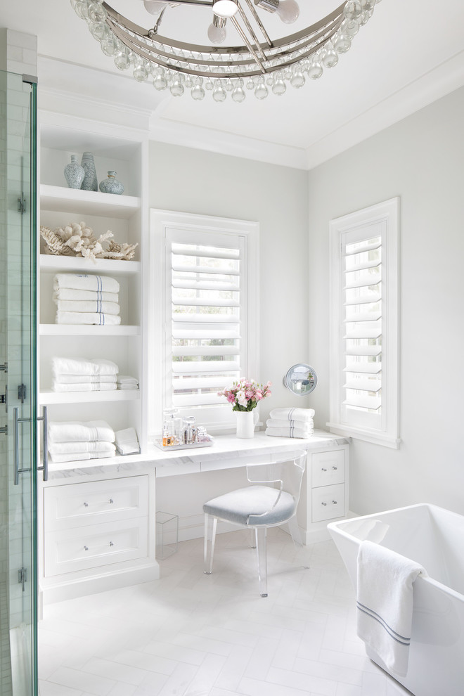 Example of a beach style white floor bathroom design in Miami with recessed-panel cabinets, white cabinets, gray walls, a hinged shower door and white countertops