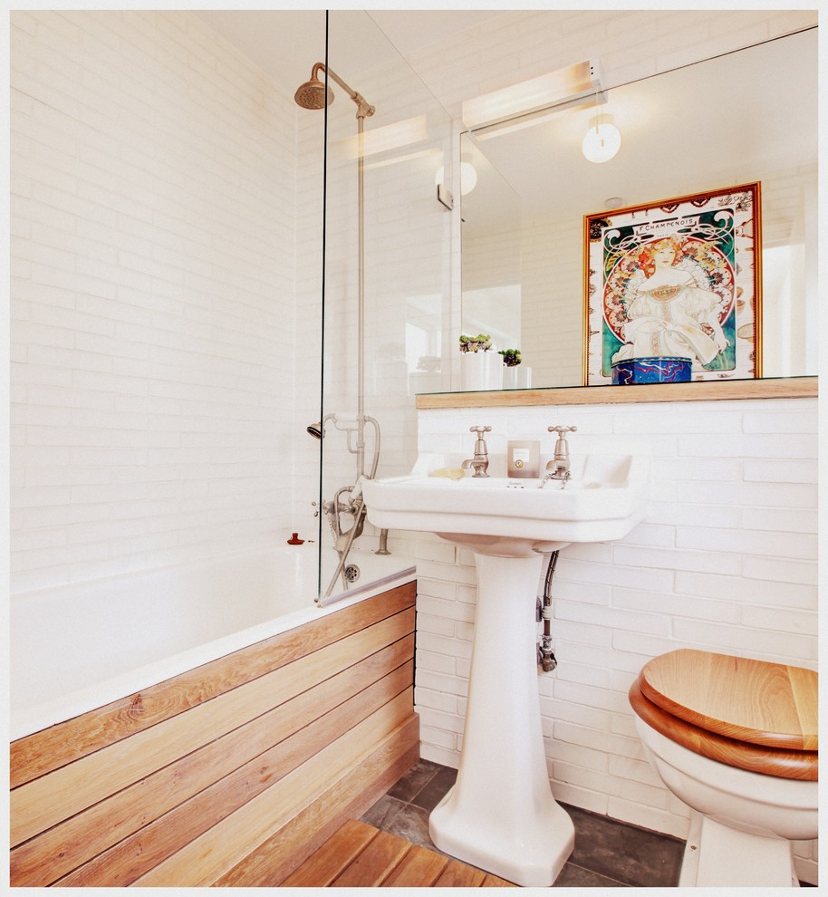 Country white tile bathroom photo in London with a pedestal sink, a two-piece toilet and white walls