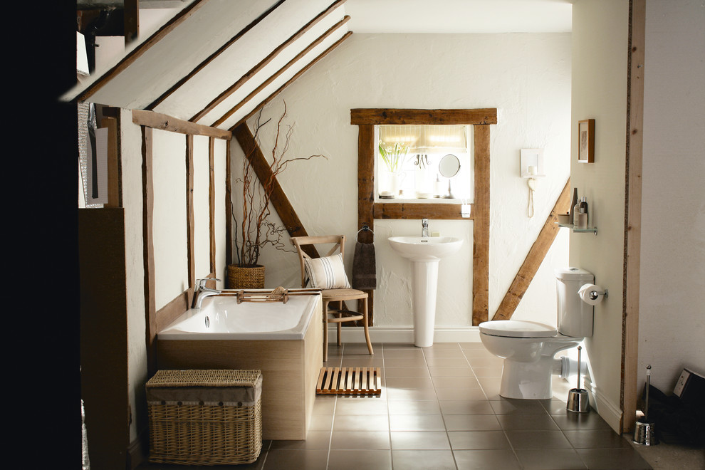 Example of a country drop-in bathtub design in West Midlands with a pedestal sink, a two-piece toilet and white walls