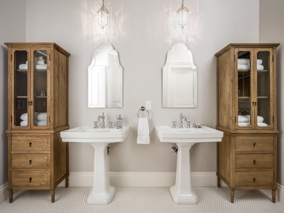 Example of a classic white tile bathroom design in Salt Lake City with a pedestal sink, glass-front cabinets and medium tone wood cabinets