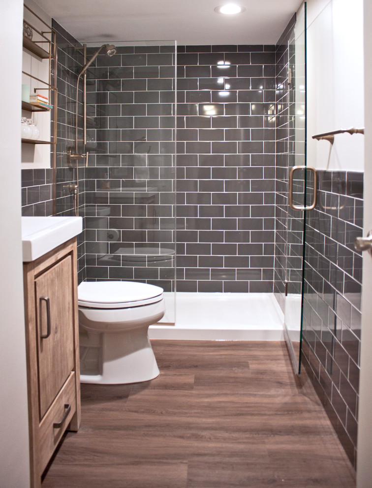 Example of a small transitional 3/4 gray tile and ceramic tile vinyl floor alcove shower design in Chicago with flat-panel cabinets, distressed cabinets, a two-piece toilet, gray walls, an integrated sink, a hinged shower door and white countertops