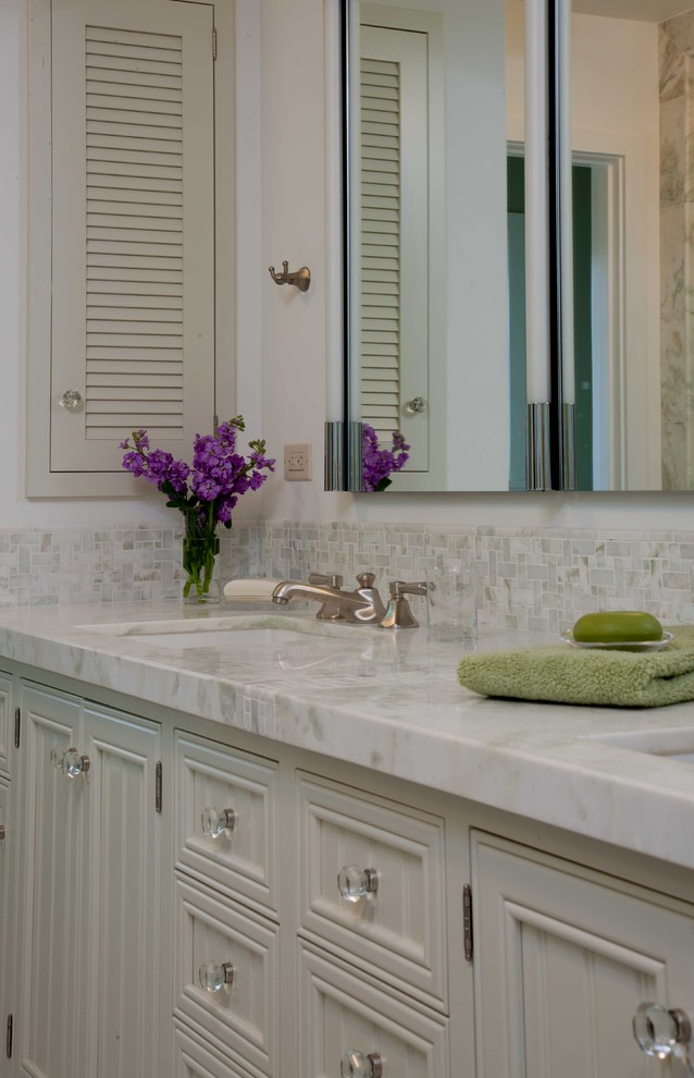 Alcove shower - mid-sized traditional master white tile and mosaic tile mosaic tile floor and white floor alcove shower idea in San Diego with recessed-panel cabinets, white cabinets, white walls, an undermount sink, marble countertops and a hinged shower door