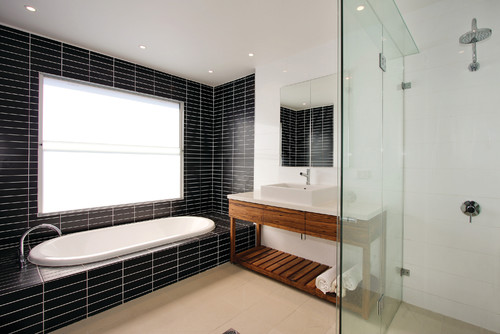 built in bath with black mosaic tile
