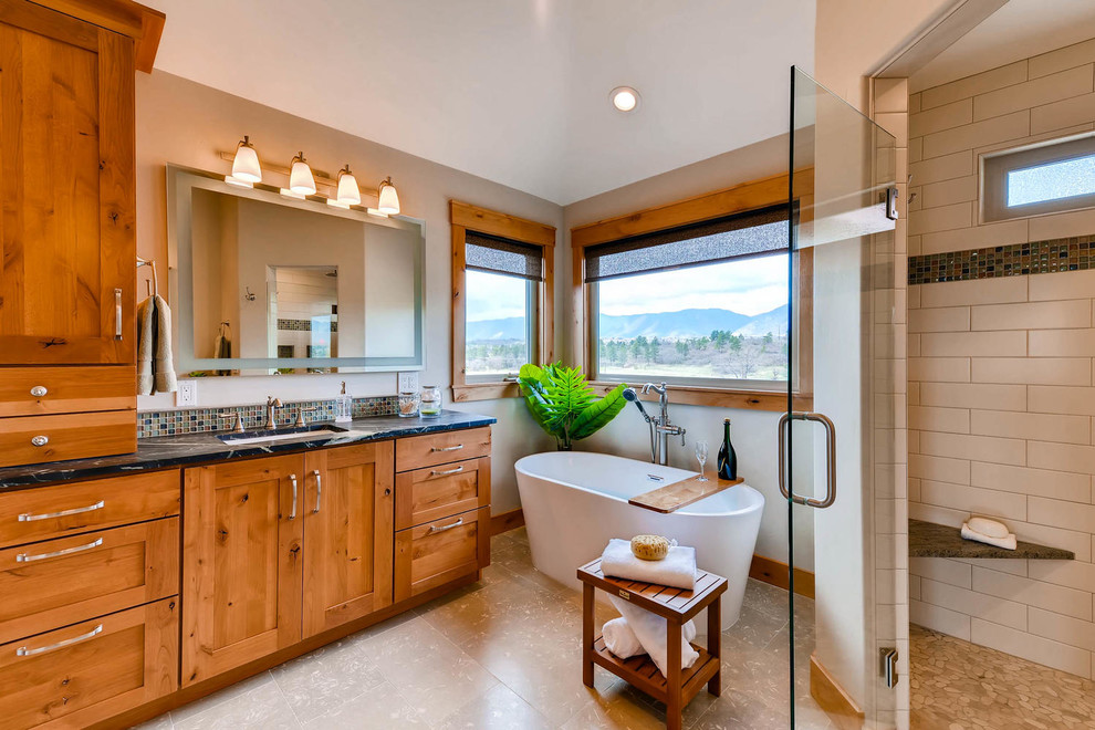 Bathroom - large craftsman master beige tile and mosaic tile limestone floor and gray floor bathroom idea in Denver with shaker cabinets, an undermount sink, soapstone countertops, medium tone wood cabinets, beige walls, a hinged shower door and a two-piece toilet