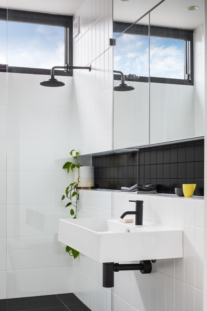 Trendy black tile and white tile black floor bathroom photo in Melbourne with white walls and a wall-mount sink