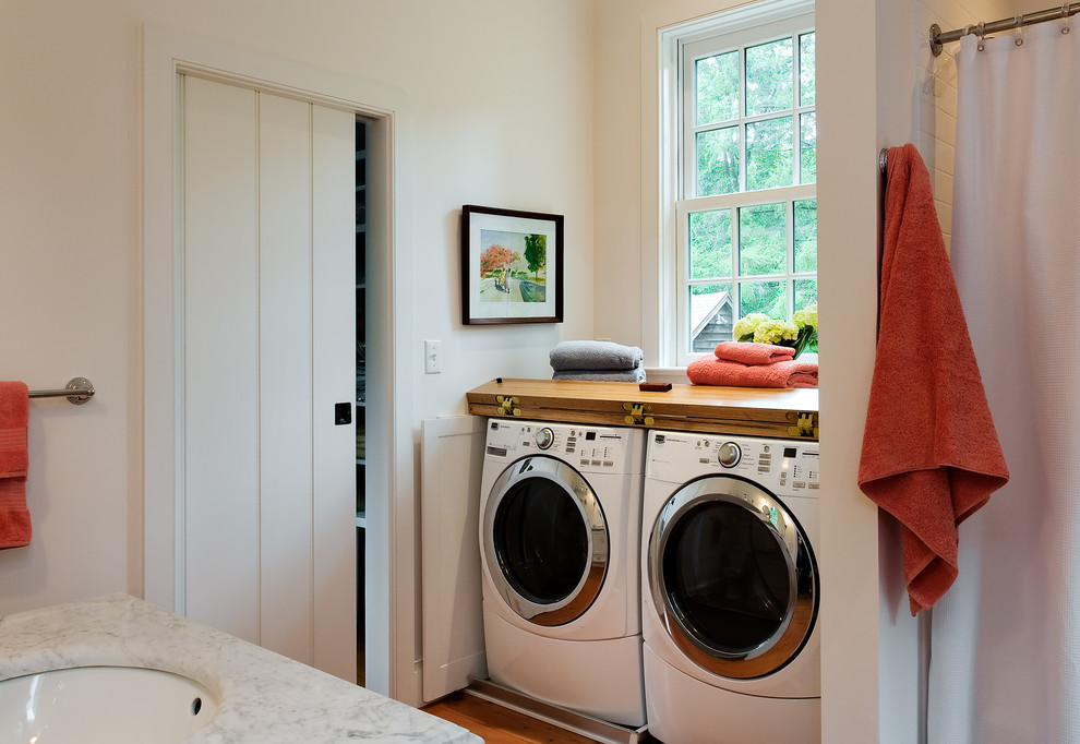 Elegant bathroom/laundry room photo in New York with marble countertops