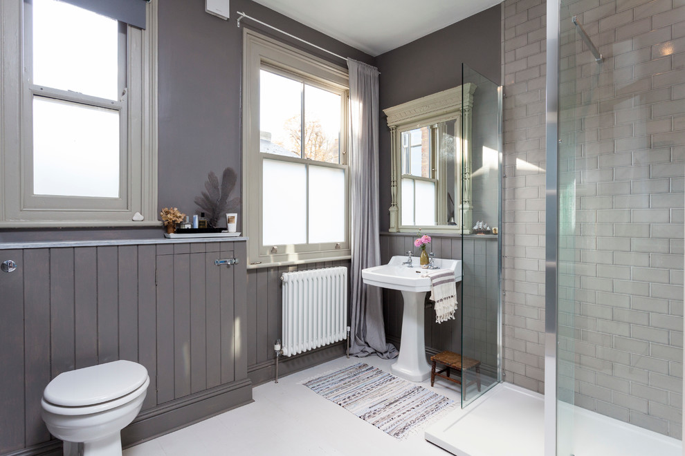 Example of a danish gray tile and subway tile corner shower design in London with a pedestal sink and gray walls