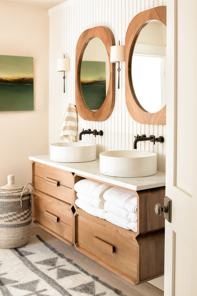 Inspiration for a coastal light wood floor and beige floor bathroom remodel in Portland Maine with medium tone wood cabinets, beige walls and a vessel sink