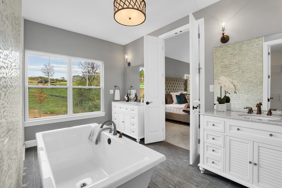 Inspiration for a cottage master ceramic tile ceramic tile and gray floor freestanding bathtub remodel in St Louis with multicolored walls, granite countertops, louvered cabinets, white cabinets and an undermount sink