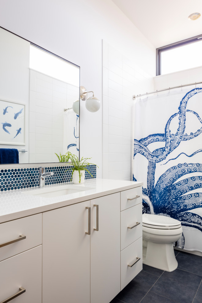 Inspiration for a contemporary white tile black floor bathroom remodel in Seattle with flat-panel cabinets, white cabinets, white walls, an undermount sink and white countertops
