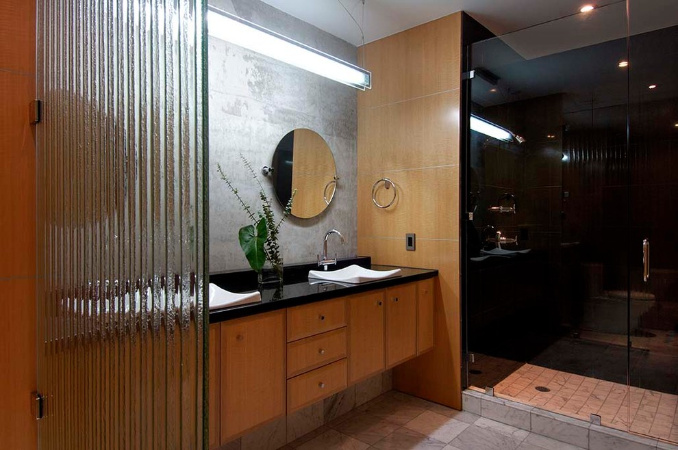 Mid-sized trendy 3/4 gray tile and cement tile ceramic tile and gray floor alcove shower photo in Hawaii with flat-panel cabinets, brown cabinets, gray walls, a vessel sink, solid surface countertops, a hinged shower door and black countertops