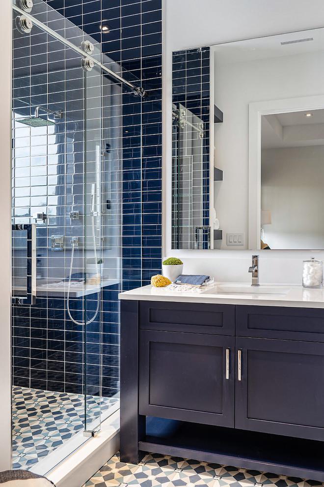 他の地域のビーチスタイルのおしゃれなバスルーム (浴槽なし) (家具調キャビネット、青いキャビネット、アルコーブ型シャワー、青いタイル、白い壁、アンダーカウンター洗面器、マルチカラーの床、引戸のシャワー、白い洗面カウンター、セメントタイルの床) の写真