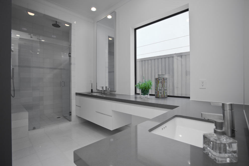 Alcove shower - contemporary white tile alcove shower idea in Dallas with an undermount sink, flat-panel cabinets, white cabinets and gray countertops