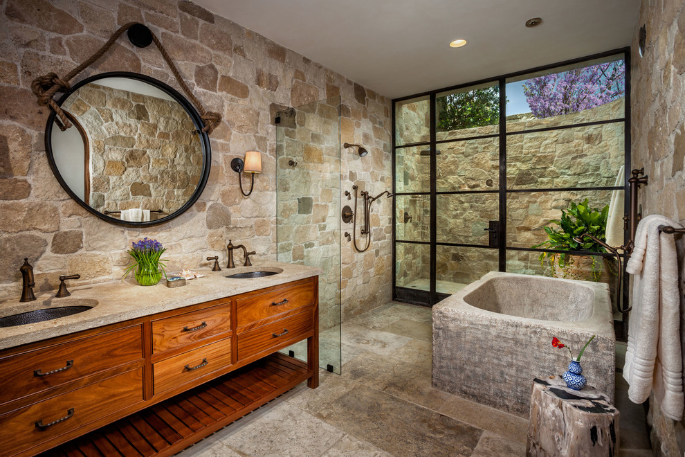 Large tuscan master beige tile and stone tile beige floor bathroom photo in Orange County with furniture-like cabinets, medium tone wood cabinets, beige walls and an undermount sink