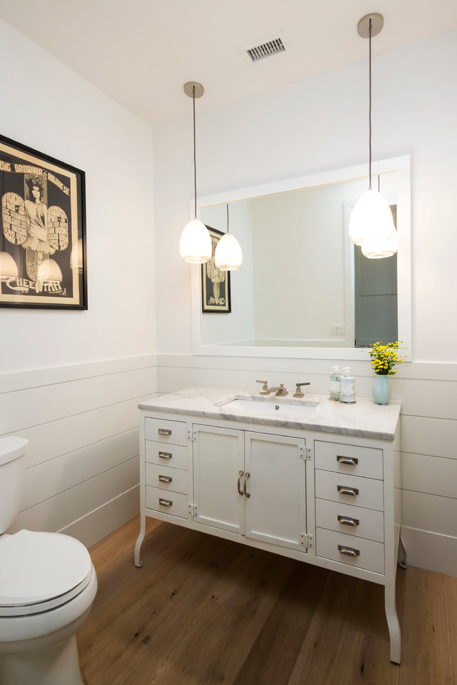 Transitional bathroom photo in Los Angeles with an undermount sink, recessed-panel cabinets, white cabinets and a two-piece toilet