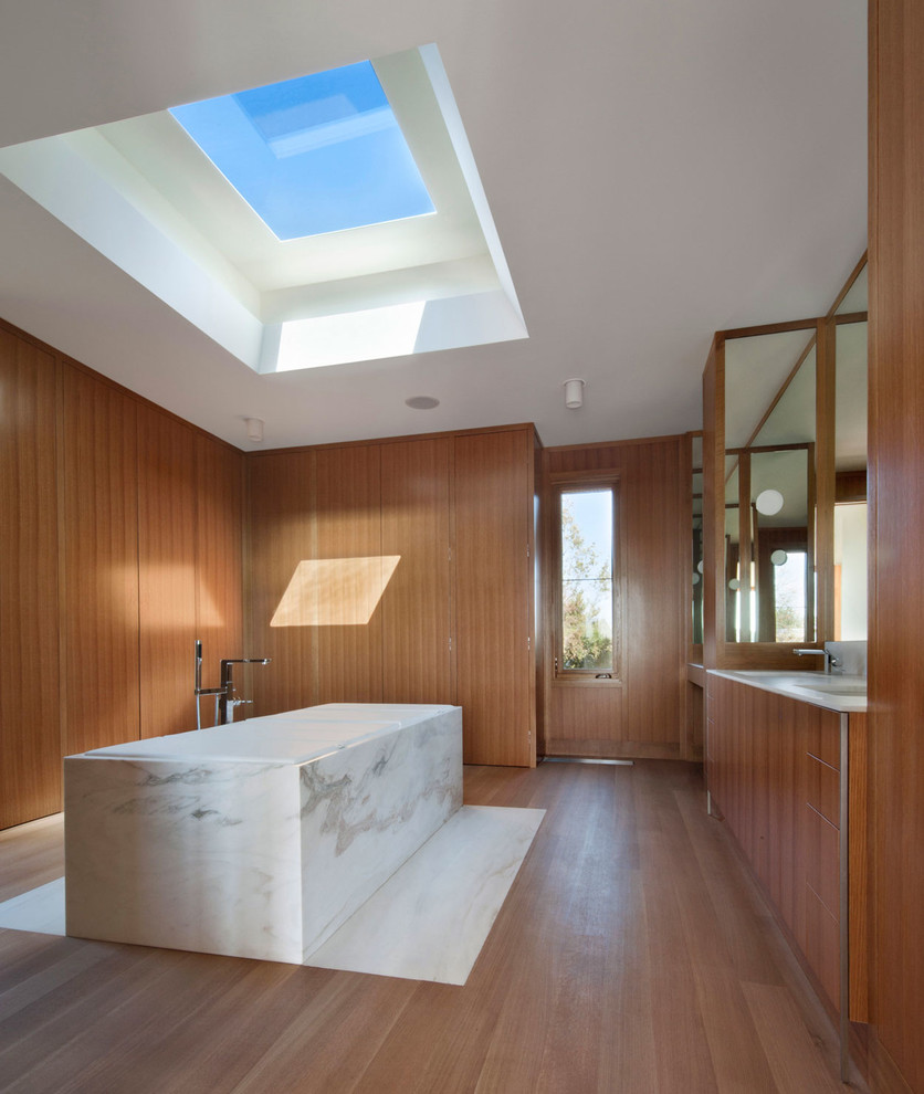 Inspiration for a large modern master white tile medium tone wood floor and brown floor freestanding bathtub remodel in New York with flat-panel cabinets, medium tone wood cabinets, marble countertops, brown walls, an undermount sink and white countertops
