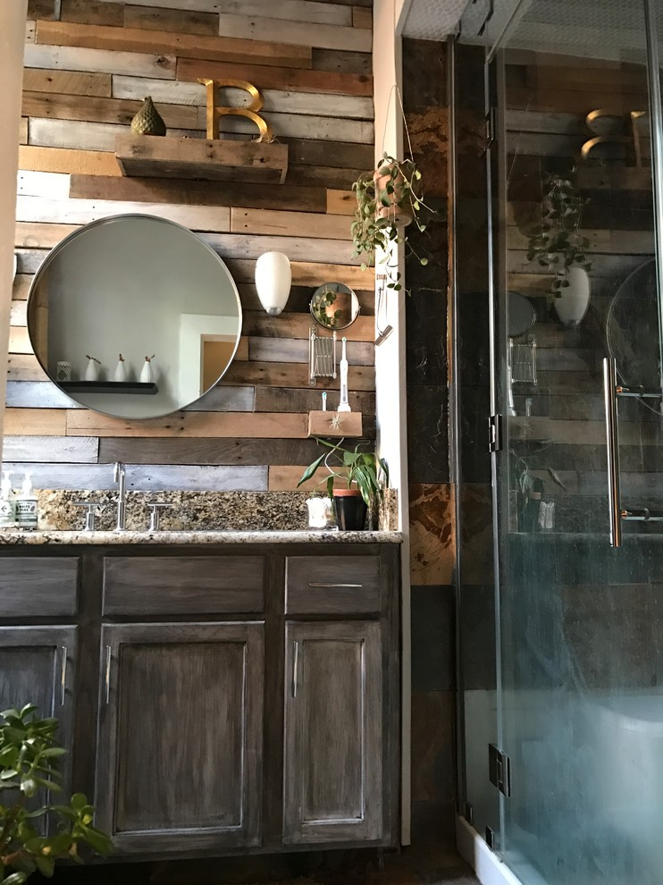 Inspiration for a mid-sized rustic master multicolored tile and mirror tile slate floor and multicolored floor bathroom remodel in New Orleans with recessed-panel cabinets, distressed cabinets, a one-piece toilet, gray walls, an undermount sink, granite countertops and a hinged shower door