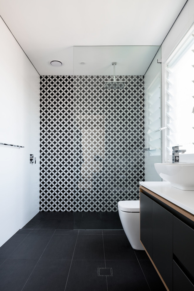 Walk-in shower - contemporary ceramic tile and black and white tile walk-in shower idea in Sydney with a vessel sink, flat-panel cabinets, black cabinets, a one-piece toilet and multicolored walls