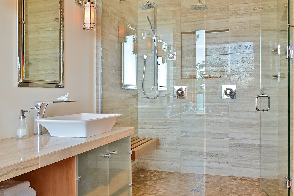 Trendy limestone tile double shower photo in Vancouver with a vessel sink