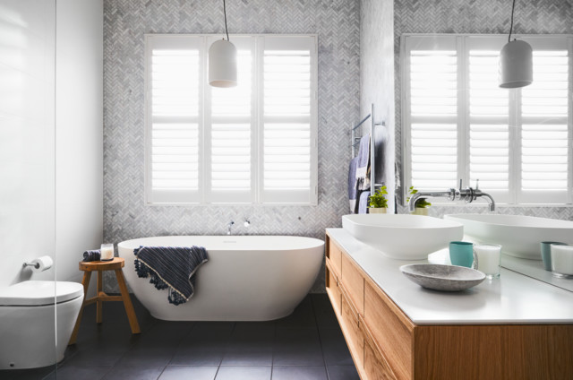 Photo of a transitional bathroom in Melbourne with flat-panel cabinets, medium wood cabinets, a freestanding tub, white walls, a vessel sink and grey floor.