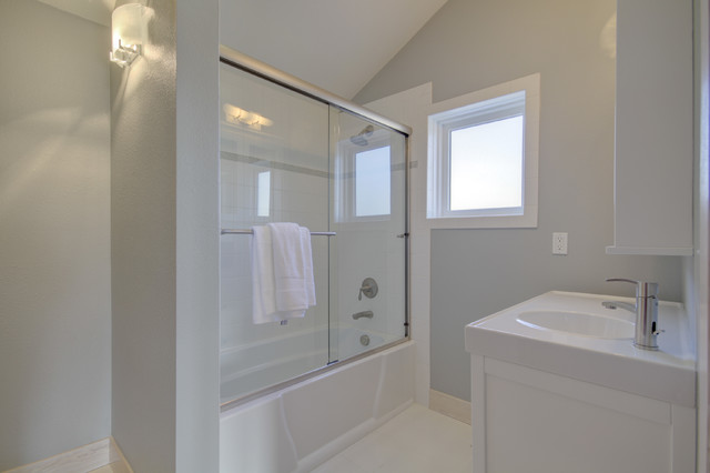 Inspiration for a mid-sized modern white tile and subway tile white floor bathroom remodel in Denver with white cabinets, gray walls and an integrated sink