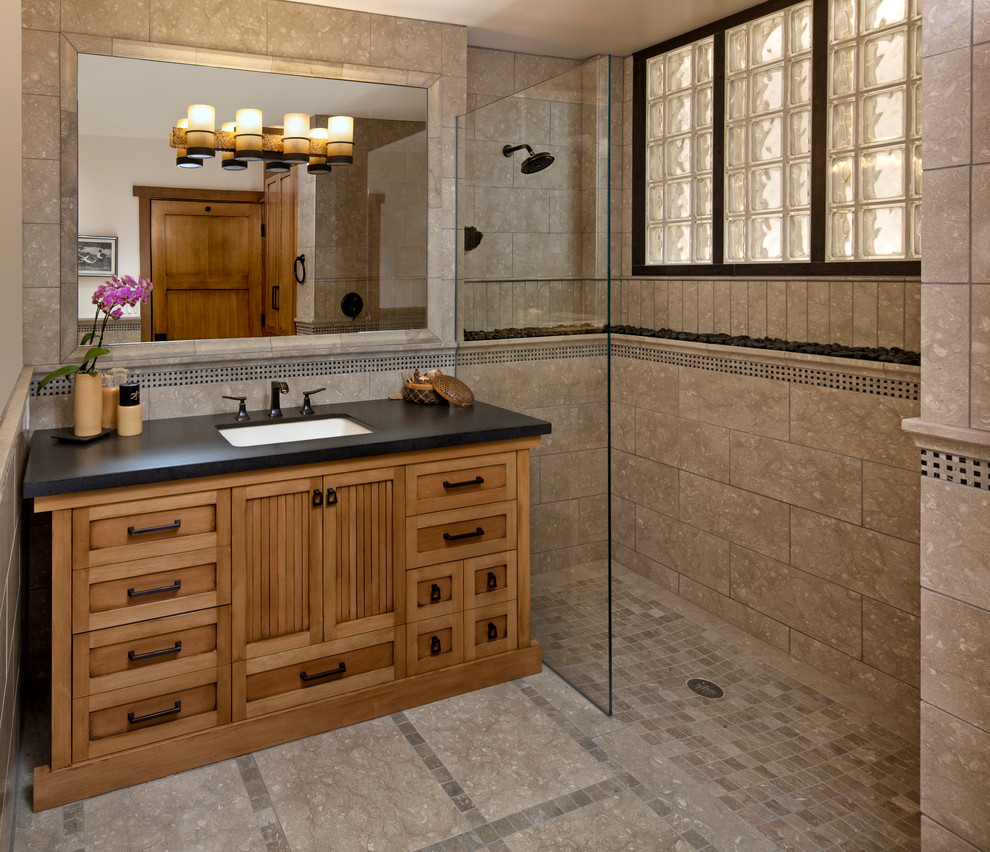 Walk-in shower - mid-sized beige tile and stone tile limestone floor walk-in shower idea in Santa Barbara with an undermount sink, medium tone wood cabinets and recessed-panel cabinets