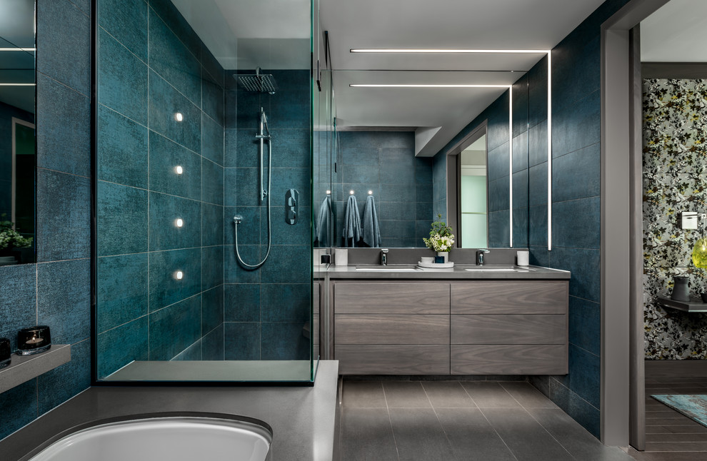 Example of a mid-sized trendy master blue tile and porcelain tile porcelain tile and gray floor corner shower design in Toronto with flat-panel cabinets, gray cabinets, an undermount tub, gray walls, an undermount sink, quartz countertops, a hinged shower door and gray countertops