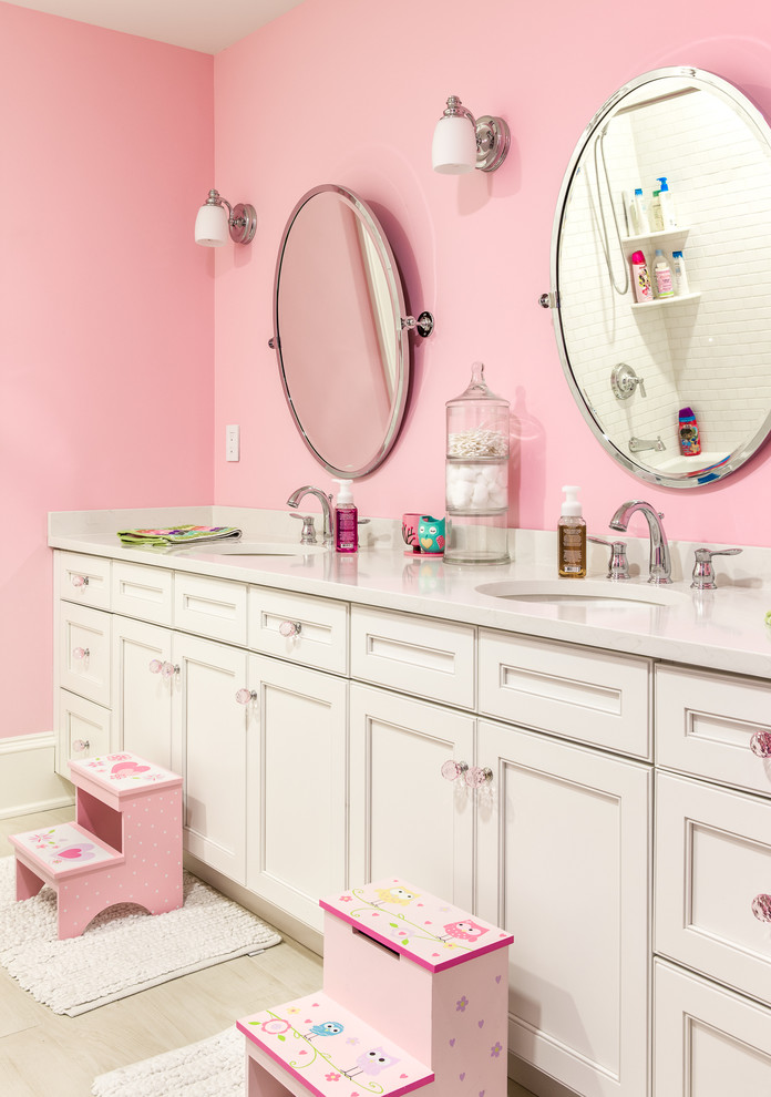 Example of a classic kids' bathroom design in New York with recessed-panel cabinets, white cabinets, pink walls and an undermount sink