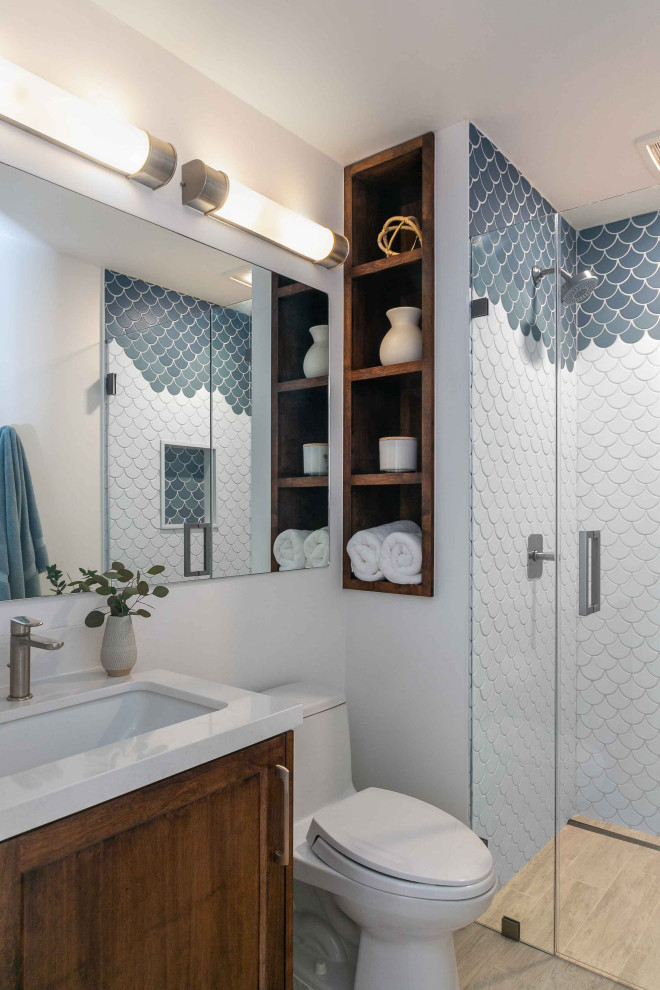Example of a transitional 3/4 blue tile and white tile light wood floor and brown floor alcove shower design in San Francisco with shaker cabinets, medium tone wood cabinets, a one-piece toilet, white walls, an undermount sink, a hinged shower door and white countertops