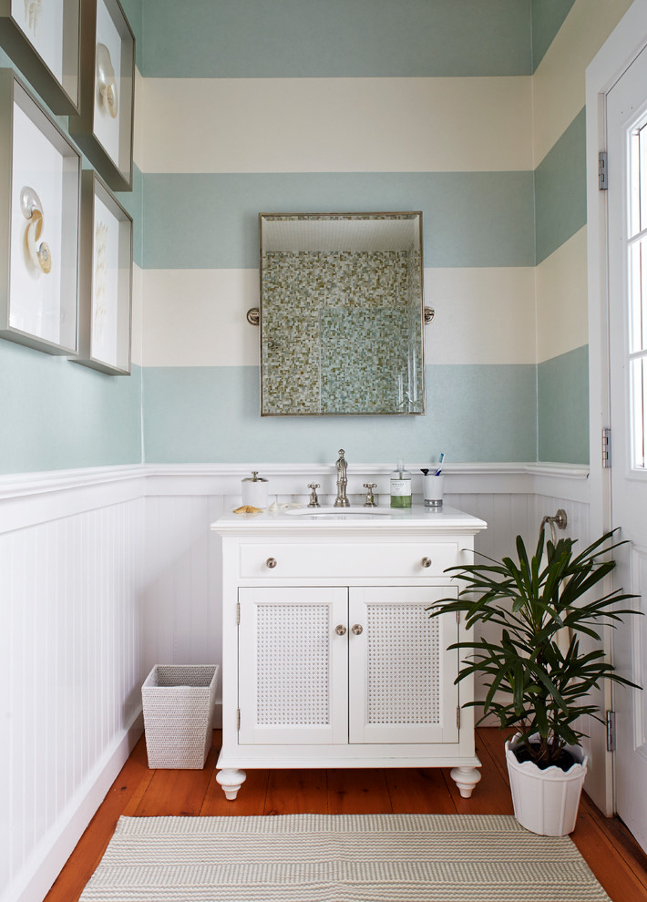 Beach style medium tone wood floor bathroom photo in New York with an undermount sink, marble countertops, white cabinets, multicolored walls and recessed-panel cabinets
