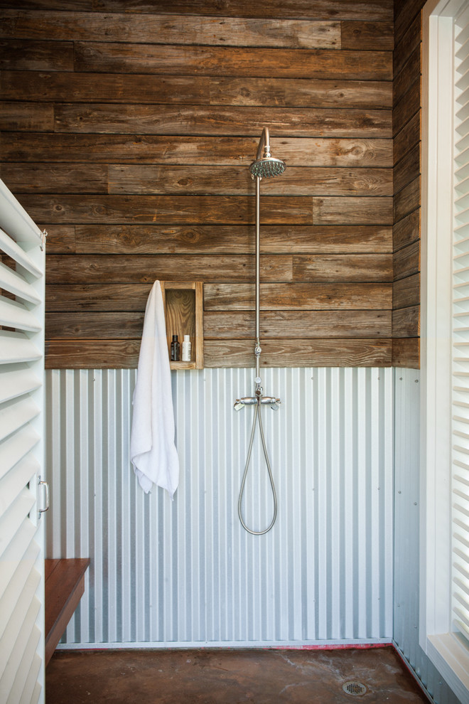Example of a small beach style concrete floor doorless shower design in Other with dark wood cabinets and a hinged shower door