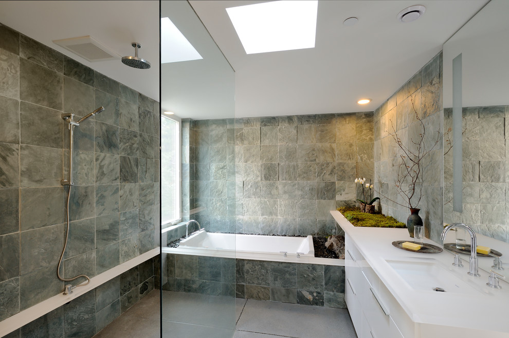 Inspiration for a mid-sized contemporary master gray tile and slate tile concrete floor bathroom remodel in Seattle with gray walls, flat-panel cabinets, white cabinets, a one-piece toilet, solid surface countertops and an undermount sink