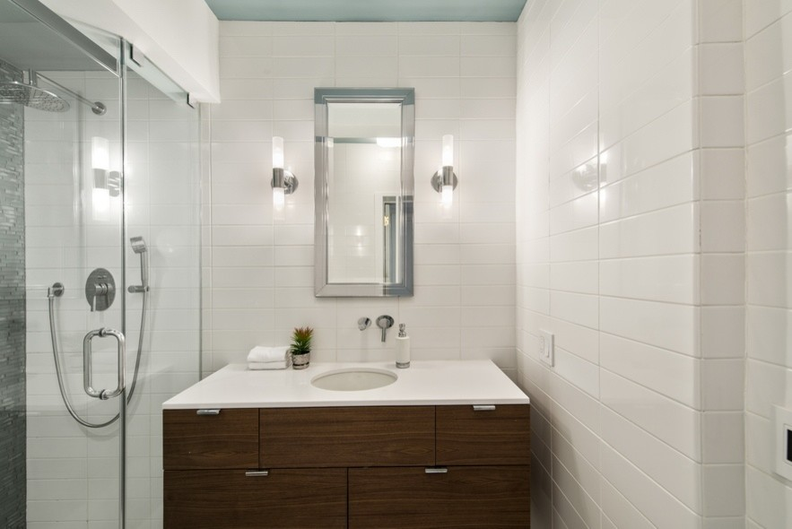 Inspiration for a small contemporary 3/4 white tile and ceramic tile alcove shower remodel in New York with flat-panel cabinets, dark wood cabinets, white walls, an undermount sink, solid surface countertops and a hinged shower door