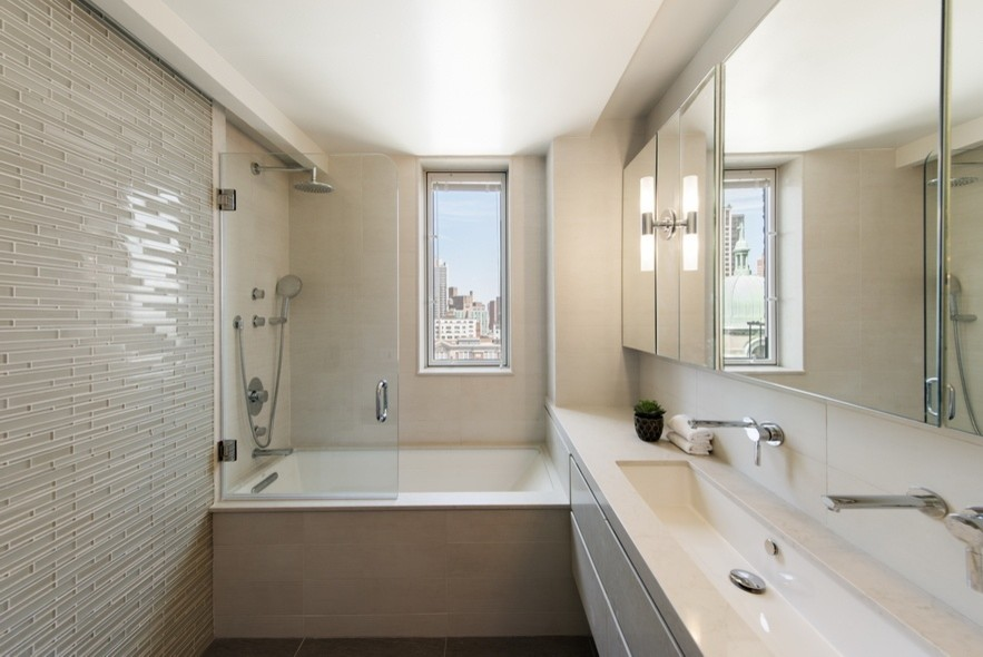Bathroom - small contemporary 3/4 gray tile and glass tile bathroom idea in New York with flat-panel cabinets, beige cabinets, an undermount tub, gray walls, a trough sink and solid surface countertops