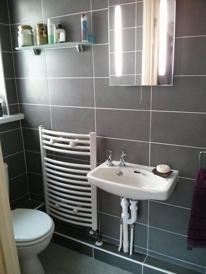 Photo of a small contemporary shower room in Essex with a wall-mounted sink, beaded cabinets, an alcove shower, a two-piece toilet, grey tiles, ceramic tiles, grey walls and mosaic tile flooring.