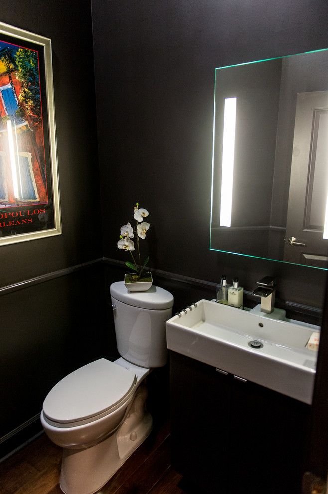 Small trendy dark wood floor bathroom photo in New Orleans with a trough sink, flat-panel cabinets, black cabinets, a one-piece toilet and brown walls