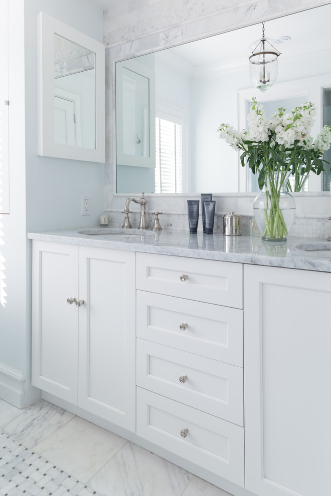 Beach style bathroom photo in New York with an undermount sink, recessed-panel cabinets, white cabinets and white walls
